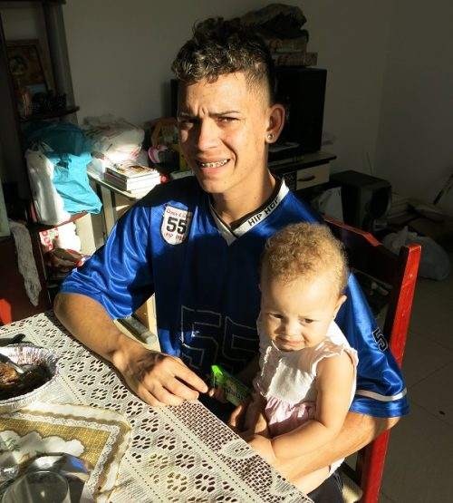 Gabriel Ani, 18, with his one-year-old daughter in their Vila Autodromo home. (Pic: Beth McLoughlin)